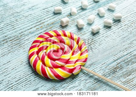 Composition with tasty colorful lollipop on wooden background, closeup