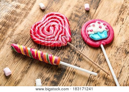 Tasty colorful lollipops on wooden background