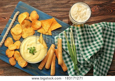Bowl with beer cheese dip and chips on wooden board