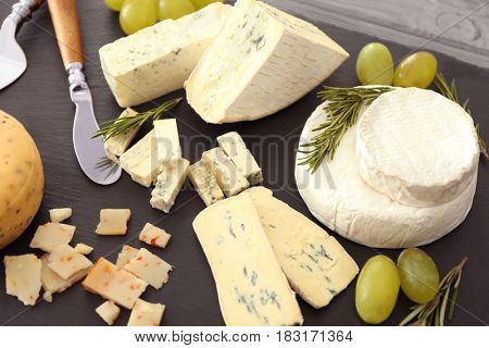 Beautiful composition of assorted cheese on slate plate