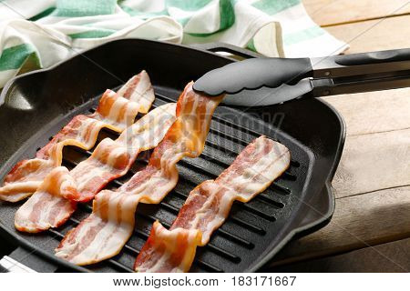 Placing bacon slice in pan with tongs, closeup