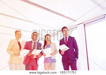 Business people holding documents while looking away in new office