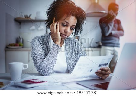 Young African american couple facing financial problem and not able to pay out debts. Desperate female holding hand on her cheek feeling stressed while managing family budget at kitchen table