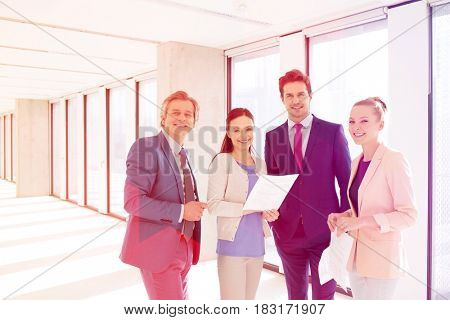 Portrait of smiling business people with documents in new office