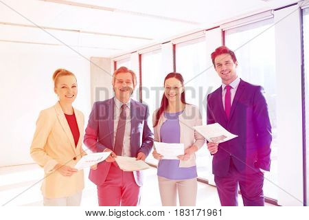 Portrait of smiling business people with documents in office
