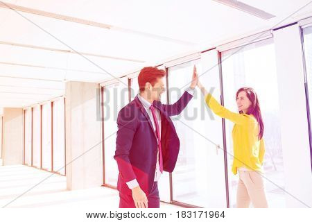 Young businessman and businesswoman high fiving in new office