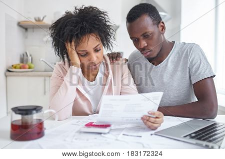 Depressed bankrupt young african american family sitting at kitchen table feeling stressed while reading notification informing about eviction from their appartment because housing debt. No money