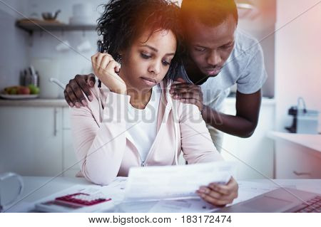 African man hugging wife while she looking at laptop using online banking app with not able to pay off gas and electricity bills. Young couple sitting at kitchen table facing financial problem