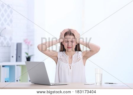 Beautiful young woman suffering from headache while sitting at table in office