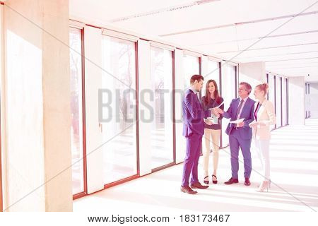 Full length of business people discussion over documents in empty office