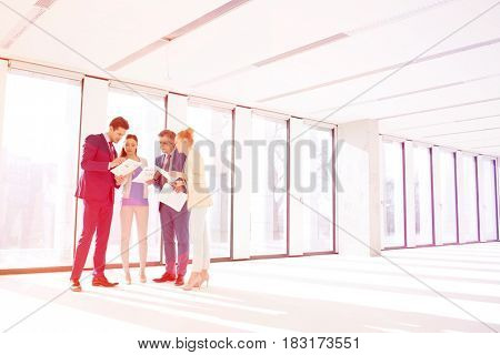 Full length of business people reviewing documents in new office
