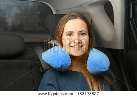 Young woman with travel pillow in car
