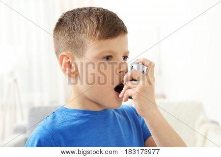 Little boy using asthma inhaler at home