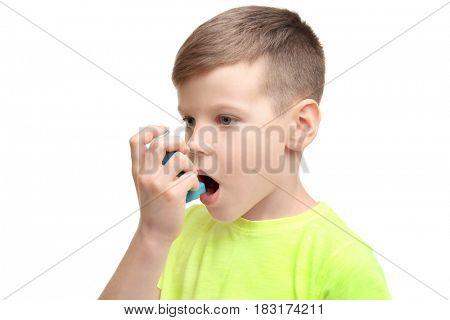 Little boy using asthma inhaler on white background
