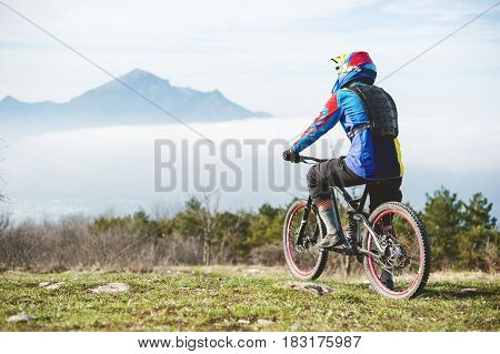 A young guy standing on your mountain bike atop a mountain, when below the mountains low clouds and fog.