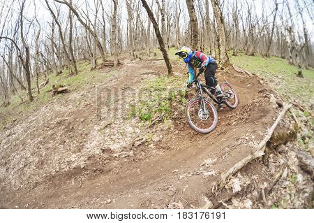 The young man in the full-face helmet passes a counter-rotation in the glide against the background of a misty forest.
