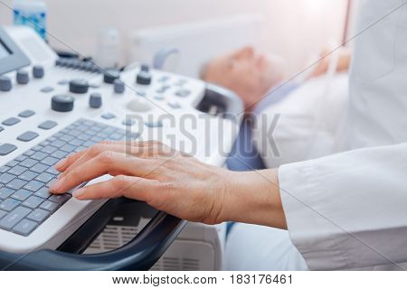 Using professional medical device. Attentive involved female doctor working in the clinic while providing ultrasonic examination for aged patient and using ultrasound machine