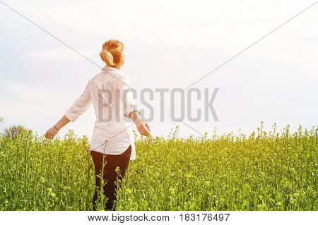 The beauty of a girl outdoors, enjoying nature and freedom and enjoying life. Beautiful girl in a white shirt, strolls on a spring field, the sun warm light. Warm green picture