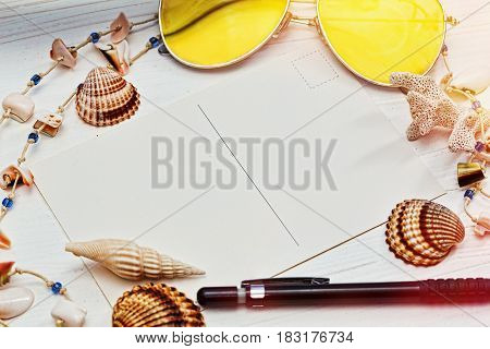 Vacations still life - blank post card and a pen surrounded by shells sunglasses and a necklace made of conches