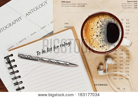Notebook with a to do list and a cup of espresso coffee on the oldened cage menu