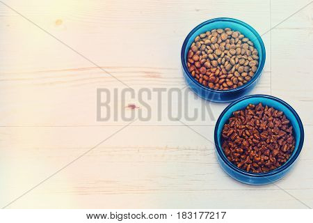 Two aquamarine bowls with different pet food standing on the floor