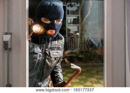 Burglar With Flashlight And Crowbar Looking Into Glass Window