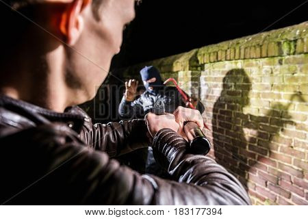 Police Officer Aiming Gun Towards Scared Burglar At Night
