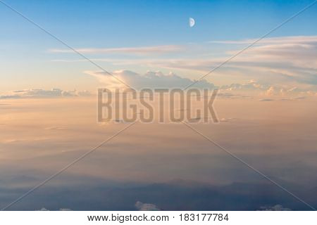 The colorful soft sky above the clouds with half moon and some mountains silhouettes below - airplane traveling in the summer