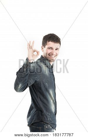 side view - stylish young man gestures OK a blank banner.the photo has a place for your text