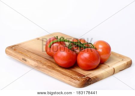 Tomatoes. Cherry On Vine On Cutting Board. Isolated On White