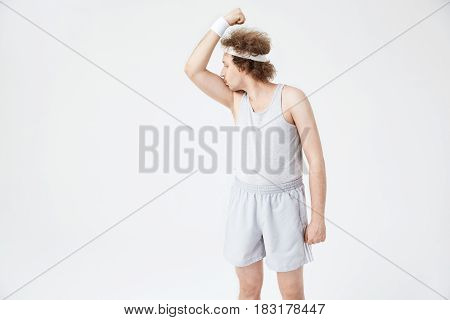 Retro guy with white headband kissing right arm biceps, being so proud of fitness success