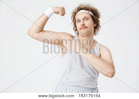 Closeup portrait of man in old-fashioned sportswear showing big guns, pointing with left hand