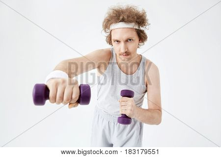 Young concentrated man working on arm muscles, training hard with dumbbells. Retro style. Looking straight