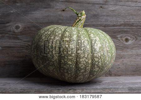 Still life - Green pumpkin on a wooden background