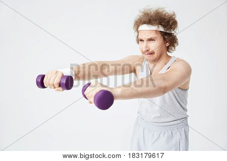 Weak retro man in old-fashioned sports wear training with hand weights. Looking exhausted