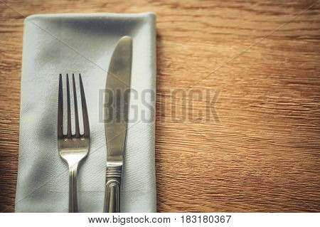 Close up shot of a fork and knife on a wooden table on a napkin.