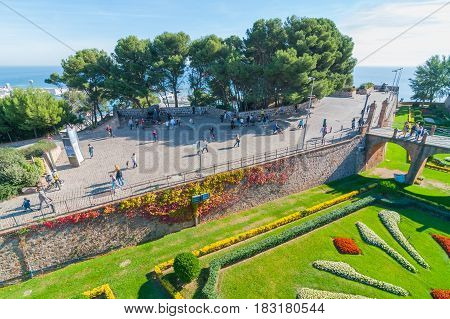 Barcelona, Spain, Nov 3rd, 2013:   People visit old fort Montjuïc Castle in Barcelona.  16th century military fortress in is now municipal facility atop of Montjuïc hill near Balearic Sea in Spain.