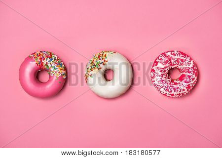 Donuts with icing on pastel pink background. Sweet donuts.