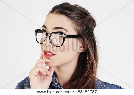 Funny young and attractive woman is thinking. Isolated on white background. Education concept.
