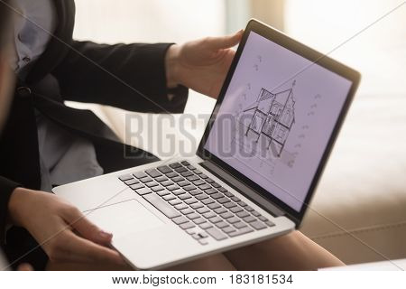 Close up of laptop in female hands with architectural plan of two story house on the screen. Realtor or building company agent showing house section cut drawing, offering property for sale