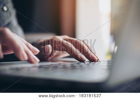 Closeup image of a business woman's hands working and typing on laptop keyboard on glass table