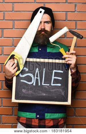 Bearded Builder Holding Various Building Tools And Board, Serious Face