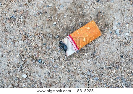 Closeup to Short Cigarette Stub on Ground