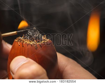 process of smoking a pipe by means of a match , close-up In the evening