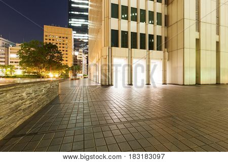 empty footpath outside of modern building at night