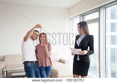 Loving happy couple just bought new dream home, starting family life, meeting with real estate agent and getting keys to own big flat, first property investment, mortgage for young family