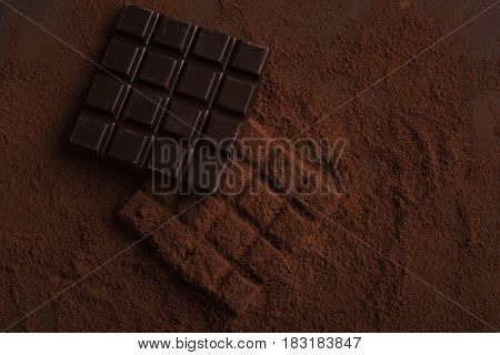 Top view of dark and milk square chocolate bars covered in powder on a surface