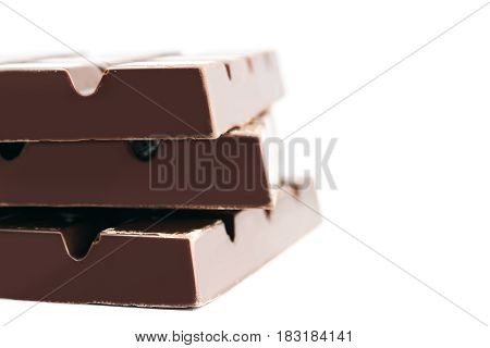 Three pieces of bitter dark chocolate bar isolated on white background close-up side view.