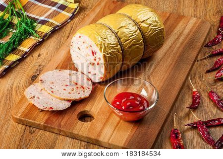 Delicious homemade sausage with hot pepper on a wooden cutting board closeup