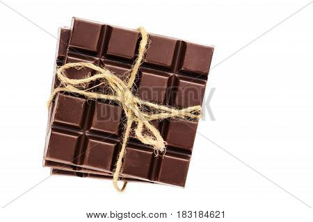Three pieces of bitter dark chocolate bar bound by twine isolated on white background close-up top view.